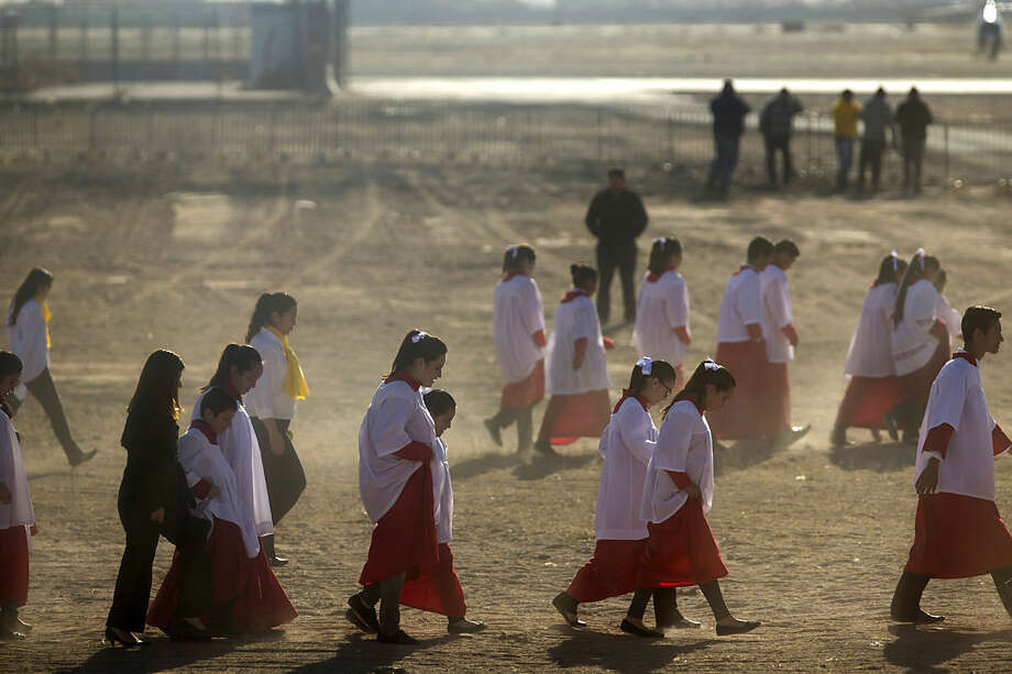Choir girls walk to the entrance of the Abraham Gonzalez International Airport to greet Pope Francis before he arrives in Ciudad Juarez, Mexico, Wednesday, Feb. 17, 2016. The pontiff is scheduled to wrap up his trip to Mexico on Wednesday with a visit in a Ciudad Juarez prison, just days after a riot in another lockup killed 49 inmates, and a stop at the Texas border when immigration is a hot issue for the U.S. presidential campaign. (AP Photo/Ivan Pierre Aguirre)