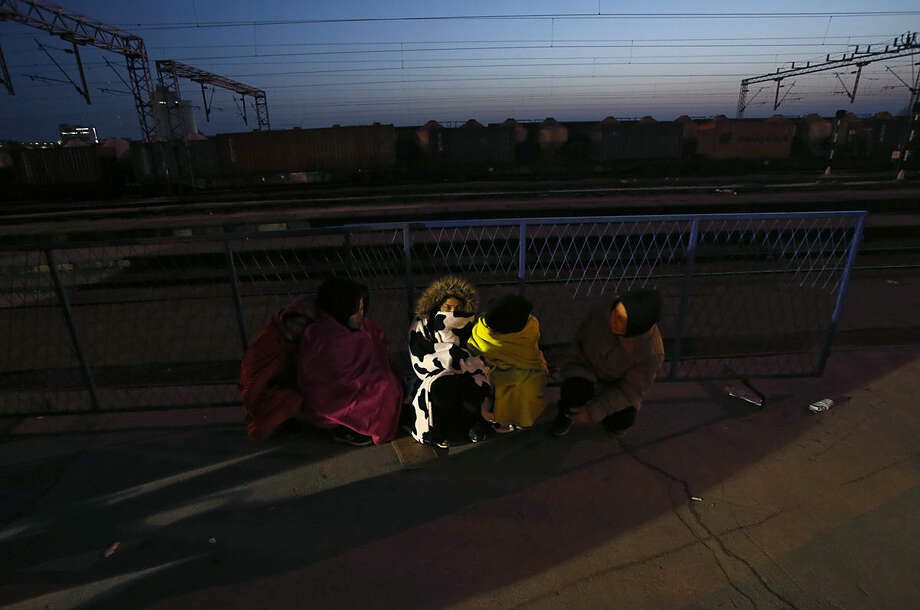 Migrants rest at the train station in Sid, about 100 km west from Belgrade, Serbia, Wednesday, Feb. 17, 2016. More than 200 people have been camping at a border train station after they were sent back to Serbia from Croatia amid tightened rules for migrants seeking entry into the European Union. (AP Photo/Darko Vojinovic)
