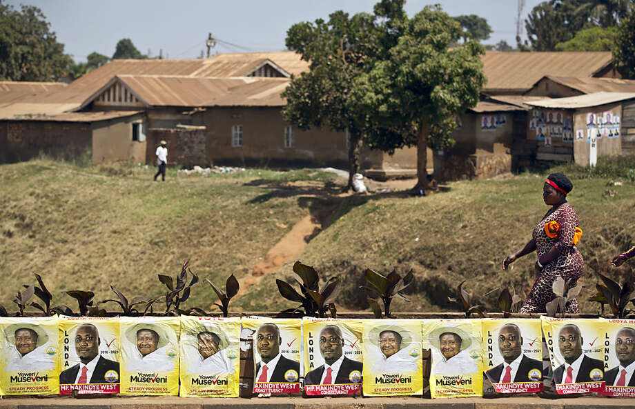 Pedestrians walk past campaign posters for long-time President Yoweri Museveni, as well as for local members of Parliament, on a street in Kampala, Uganda Wednesday, Feb. 17, 2016. On the eve of presidential elections, a heavy police and military presence can be seen in the capital Kampala. (AP Photo/Ben Curtis)