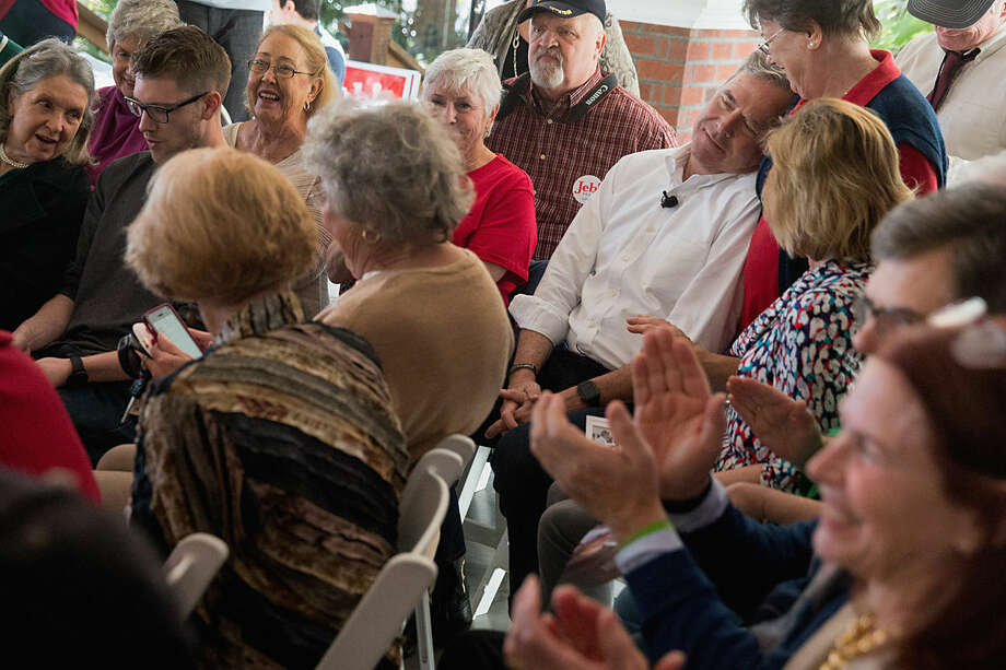 Republican presidential candidate, former Florida Gov. Jeb Bush, top right, leans his head against a member of the audience as he sits in the audience before being introduced to speak at a rally at Summerville Country Club in Summerville, S.C., Wednesday, Feb. 17, 2016. (AP Photo/Andrew Harnik)