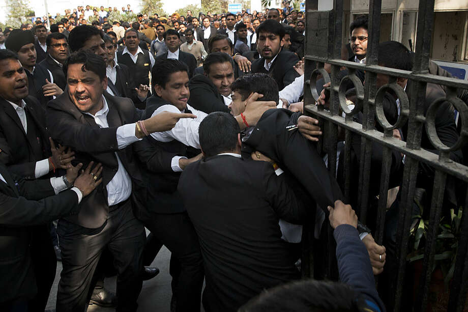 A lawyer, center, who spoke to the media supporting student leader Kanhaiya Kumar, is beaten up by other lawyers outside a Delhi court, in New Delhi, India, Wednesday, Feb. 17, 2016. Dozens of lawyers, many with links to India's ruling nationalist party, clashed Wednesday with protesters demanding the release of a student leader arrested under India's colonial-era sedition laws. (AP Photo/Tsering Topgyal)