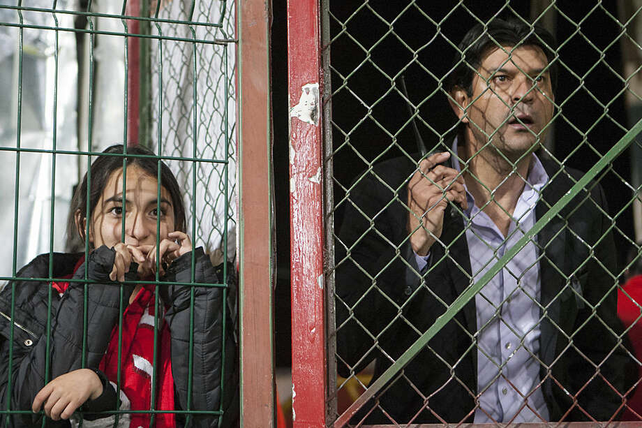 Mexico's Toluca coach Jose Cardozo, right, watches the game from behind a chain link fence after he was sent off by the referee, during a Copa Libertadores soccer match against Brazil's Gremio, in Toluca, Mexico, Wednesday, Feb. 17, 2016. (AP Photo/Christian Palma)