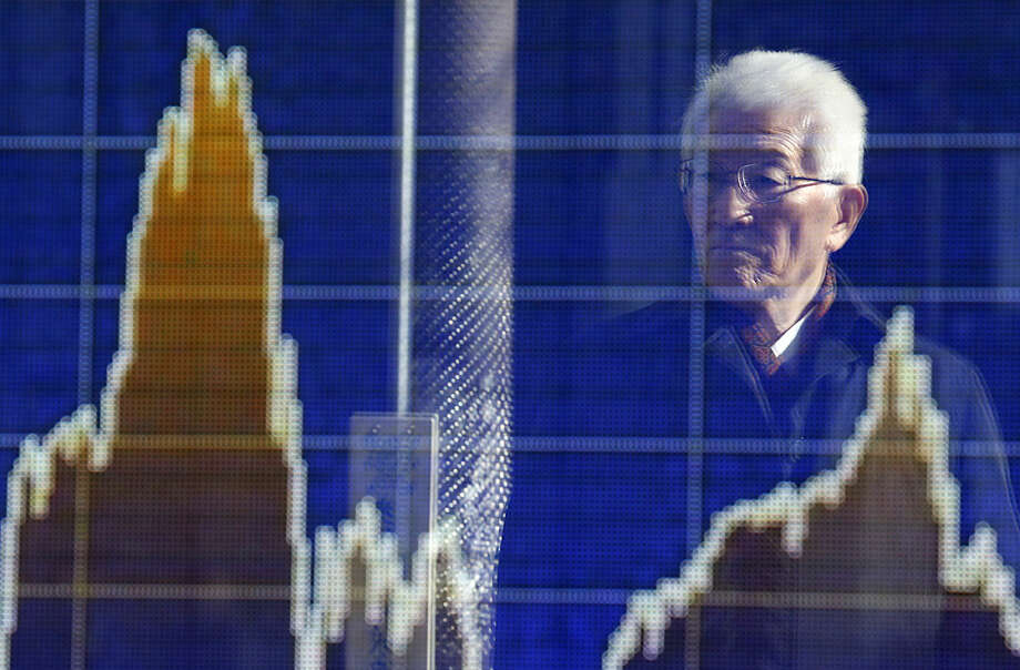 A man is reflected on the electronic board of a securities firm in Tokyo, Wednesday, Feb. 17, 2016. Asian stock markets were mostly higher Wednesday as investors weighed the potential outcome of a preliminary agreement between Russia and Saudi Arabia to hold off on further increases in crude oil production, possibly alleviating a growing glut in supply. (AP Photo/Shizuo Kambayashi)