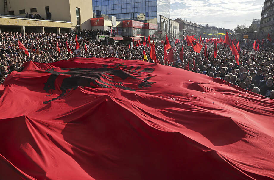 A massive Albanian flag is carried on top of tens of thousands of Kosovo opposition supporters during anti-government rally in Kosovo's capital Pristina on Wednesday, Feb. 17, 2016. Kosovo opposition supporters called for the government to resign Wednesday on the eighth anniversary of the country's declaration of independence, accusing it of violating the country's constitution in reaching deals with Serbia and Montenegro. (AP Photo/Visar Kryeziu)