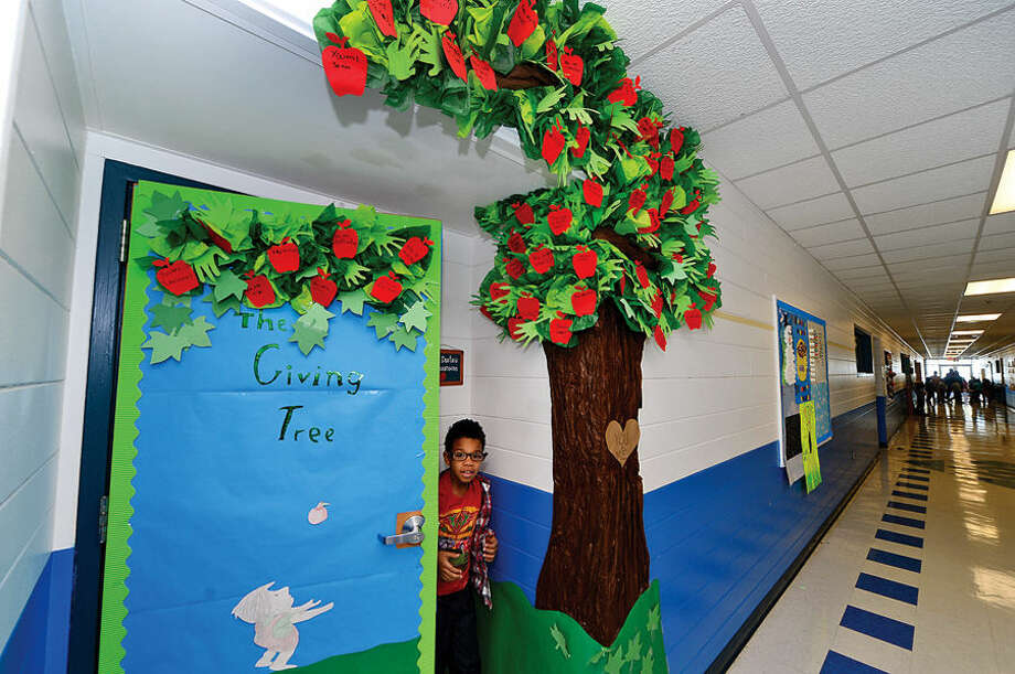 Hour photo / Erik Trautmann Kendall Elementary School student, Jacqai Singleton, exits his second grade class under their Giving Tree Tuesday which was adorned with positive messages from classmates as part of the school's Great Kindness Challenge, an anti-bullying and positive citizenship program.