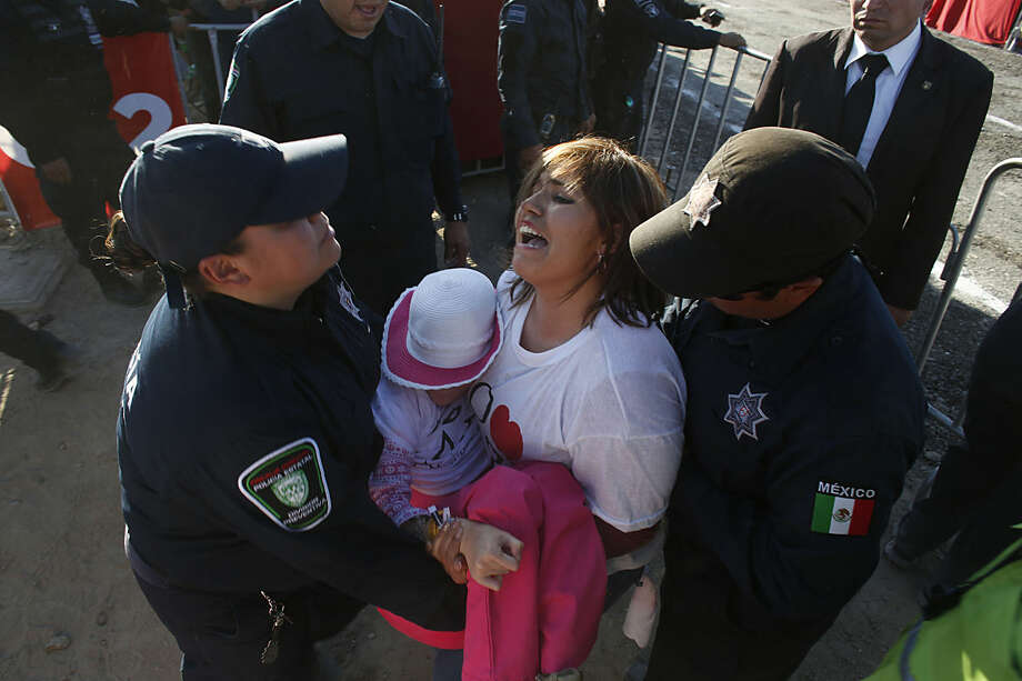 A woman holding a child is led away by police after she tried to stop the motorcade of Pope Francis as he arrived for a massive open-air Mass in a park just a few meters from the U.S. border in Ciudad Juarez, Mexico, Wednesday, Feb. 17, 2016. Thousands of people from El Paso as well as other parts of the U.S. were expected to make the short trip over the various bridges that link the cities to attend the outdoor Mass that is expected to be attended by more than 200,000 people and will cap Francis' visit to Mexico. (AP Photo/Dario Lopez-Mills)