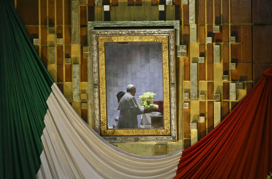 Pope Francis, reflected in the frame that holds the image of the Virgin of Guadalupe, holds a bouquet of flowers as he prays to her inside the Basilica built in her honor in Mexico City, Saturday, Feb. 13, 2016. The pontiff's five-day visit included a prayer before the Virgin of Guadalupe shrine, the largest and most important Marian shrine in the world and one that is particularly important to the first Latin American pope. (AP Photo/Gregorio Borgia)