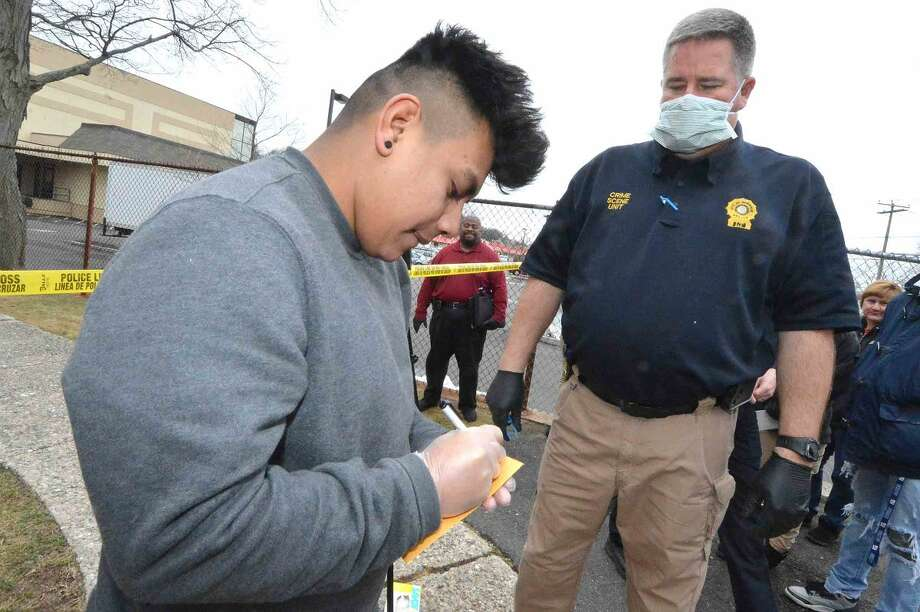 Hour Photo/Alex von Kleydorff Daniel Iniestra processes a bag of evidence for Norwalk Police Lt . Art Weisberger, Commander of the Crime Scene Unit during a mock crime scene classroom at Norwalk Pathways Academy at Briggs