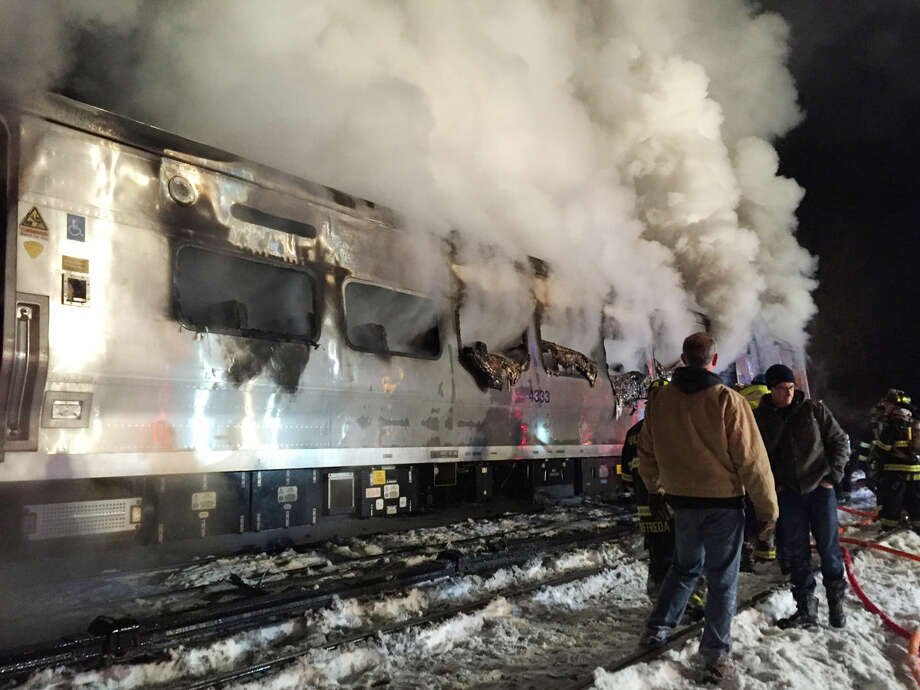 A Metro-North Railroad passenger train smolders after hitting two vehicles in Valhalla, N.Y., Tuesday, Feb. 3, 2015. (AP Photo/The Journal News, Frank Becerra Jr) NYC METRO OUT, TV OUT, MAGS OUT, NO SALES