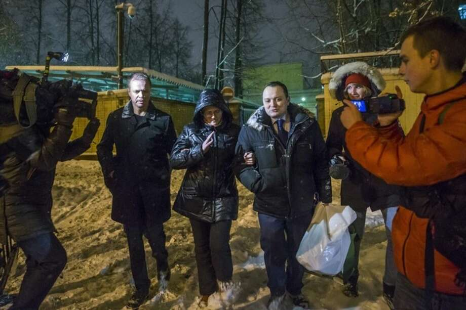 Svetlana Davydova, center, a mother of seven, who lives in the city of Vyazma in western Russia and was arrested last month on treason charges for providing Ukraine with information on Russian troops movements, walks with two unidentified men after she was released for a prison in Moscow, Russia, Tuesday, Feb. 3, 2015. The husband of a Russian mother of seven suspected of spying for Ukraine said Tuesday he was summoned for questioning but refused to answer any questions, as pressure grew on the Kremlin to release her. (AP Photo/Pavel Golovkin)