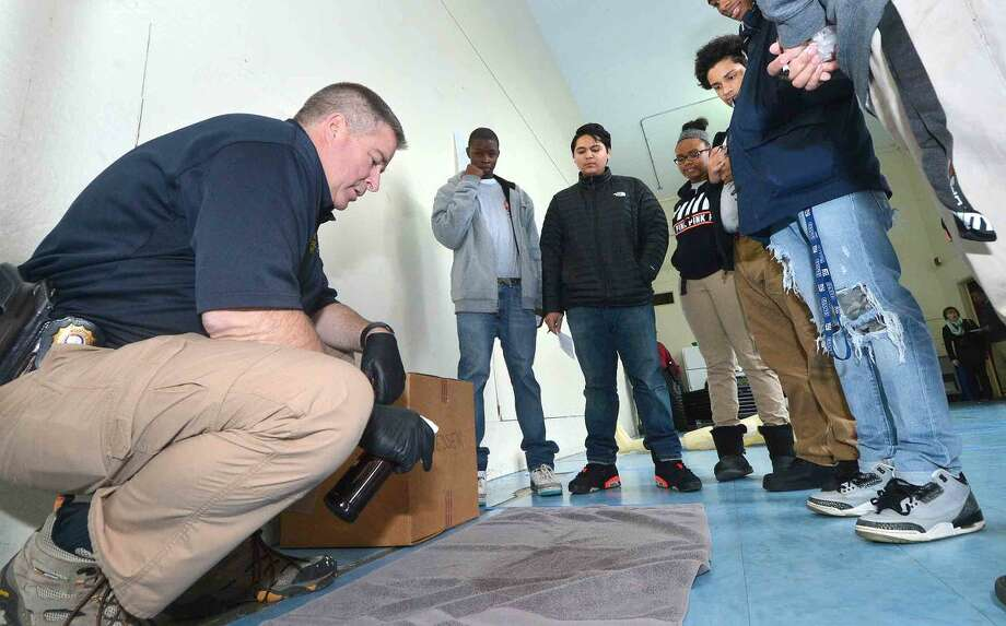 Hour Photo/Alex von Kleydorff Norwalk Police Lt . Art Weisberger, Commander of the Crime Scene Unit looks for evidence during a mock crime scene classroom at Norwalk Pathways Academy at Briggs
