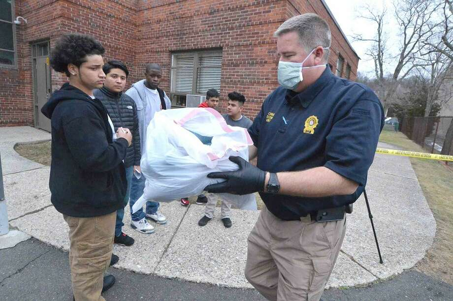 Hour Photo/Alex von Kleydorff Norwalk Police Lt . Art Weisberger, Commander of the Crime Scene Unit gathers some evidence during a mock crime scene classroom at Norwalk Pathways Academy at Briggs