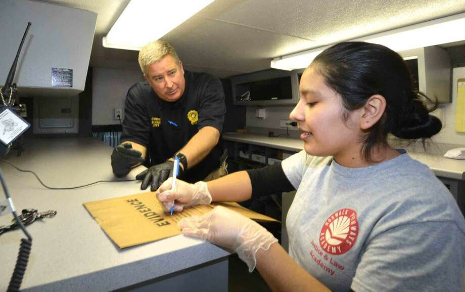 Hour Photo/Alex von Kleydorff Norwalk Police Lt . Art Weisberger, Commander of the Crime Scene Unit works with Evelyn Buceta, while investigating a mock crime scene for the students at Norwalk Pathways Academy at Briggs Justice and Law Academy.