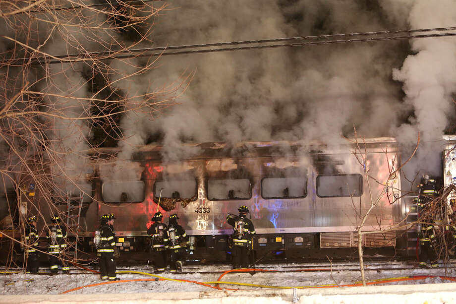 A Metro-North Railroad passenger train smolders after hitting two cars in Valhalla, N.Y., Tuesday, Feb. 3, 2015. (AP Photo/The Journal News, Frank Becerra Jr) NYC METRO OUT, TV OUT, MAGS OUT, NO SALES