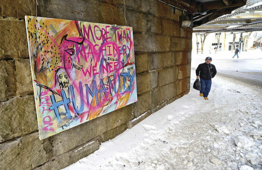 "Hour photo / Erik TrautmannA pedestrian walks by newly installed graffiti painting on canvas hung under the Washington Street train bridge that reads, ""More Than Machinery, We Need Humanity"" in SoNo Tuesday."