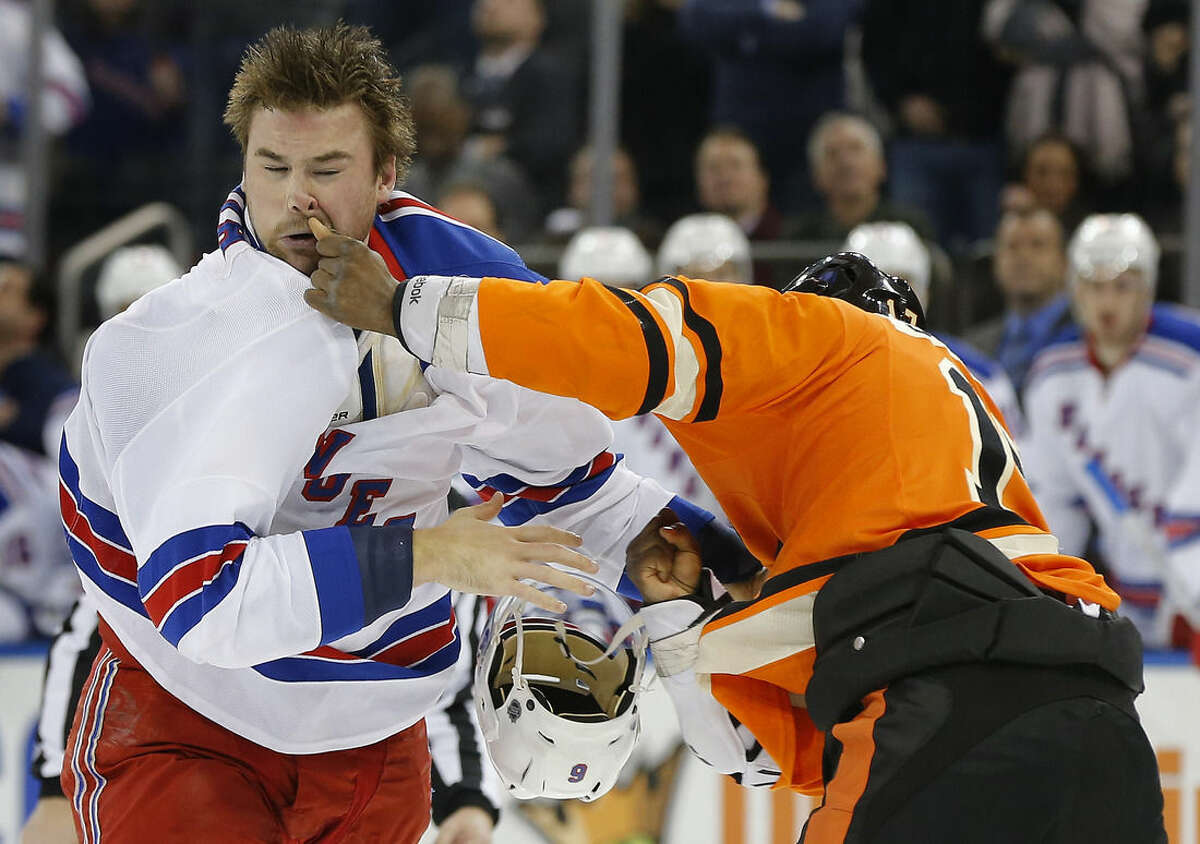 New York Rangers defenseman Dylan McIlrath, left, fights with Philadelphia Flyers right wing Wayne Simmonds during the first period of an NHL hockey game, Sunday, Feb. 14, 2016, in New York. (AP Photo/Julie Jacobson)