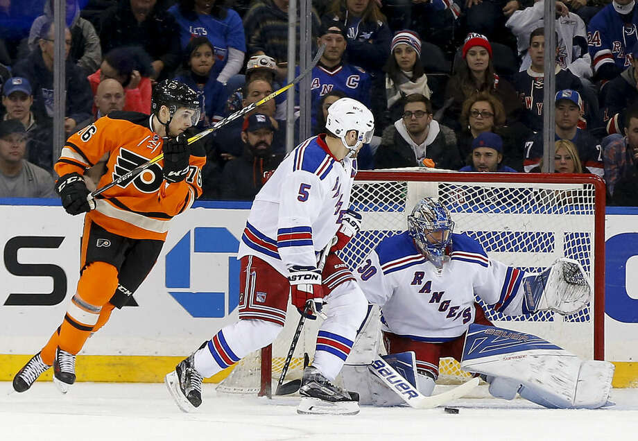 Philadelphia Flyers center Chris VandeVelde (76) and New York Rangers defenseman Dan Girardi (5) look for the rebound as goalie Henrik Lundqvist (30) blocks a shot during the second period of an NHL hockey game, Sunday, Feb. 14, 2016, in New York. (AP Photo/Julie Jacobson)