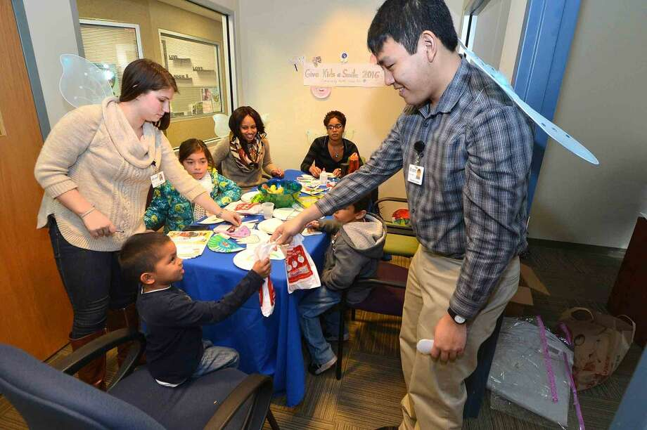 Hour Photo/Alex von Kleydorff At the coloring table Americorps member Raymond Uymatiao hands out goodie bags with Toothbrushes and toothpaste to kids at The Community Health Center for Give a Kid a Smile Day