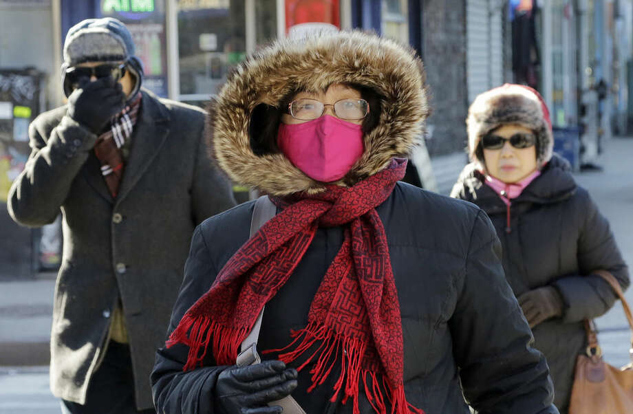 People are bundled up as they walk in cold weather, Sunday, Feb. 14, 2016, in the Queens borough of New York. Bitter temperatures and biting winds had much of the northeastern United States bundling up this weekend. (AP Photo/Mark Lennihan)