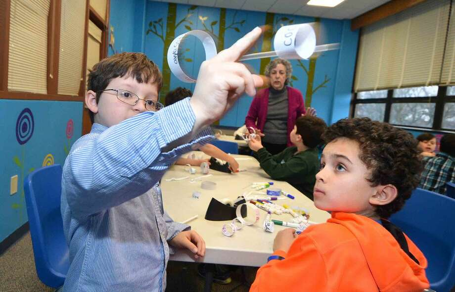 Hour Photo/Alex von Kleydorff Matthew Calle gets his Hoop Glider airborn for the first time as Cameron Rice watches, during a Super Science program at the Norwalk Public Library on Tuesday