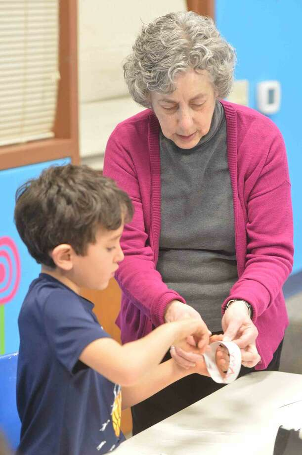 Hour Photo/Alex von Kleydorff Library Assistant Jean Goldsteirn helps Emmett Rice get his Hoop Glider connected properly as kids learn about the science of aerodynamics and flight at the Norwalk Library's Super Science program