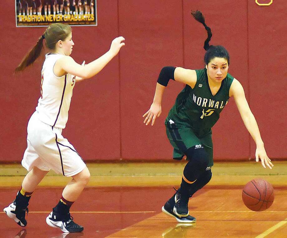 Hour photo/John Nash - Norwalk's Tatiana Arias, right, pushes the ball up the court against the pressure of St. Joseph defender Alyssa Zito during the second half of Wednesday's FCIAC girls basketball game in Trumbull. Norwalk won 48-44.