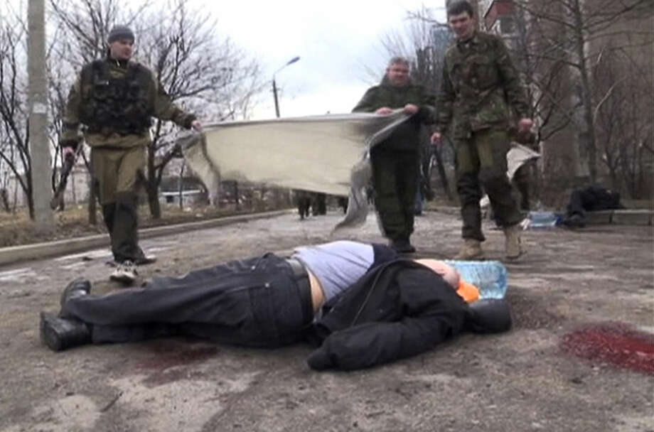 In this screen shot made available by RU-RTR, pro-Russia rebels cover a body of a victim outside clinic 27, damaged after shelling, in Donetsk, Ukraine, Wednesday, Feb. 4, 2015. Heavy shelling in the rebel stronghold of Donetsk in eastern Ukraine on Wednesday afternoon killed at least five people and damaged a hospital, six schools and five kindergartens, local officials said. (AP Photo/RU-RTR) TV OUT