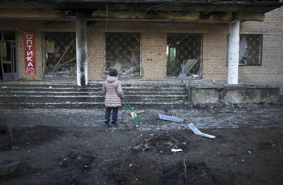A woman stands outside clinic 27, damaged after shelling, in Donetsk, Ukraine, Wednesday, Feb. 4, 2015. Heavy shelling in the rebel stronghold of Donetsk in eastern Ukraine on Wednesday afternoon killed at least five people and damaged a hospital, six schools and five kindergartens, local officials said. (AP Photo/Vadim Braydov)