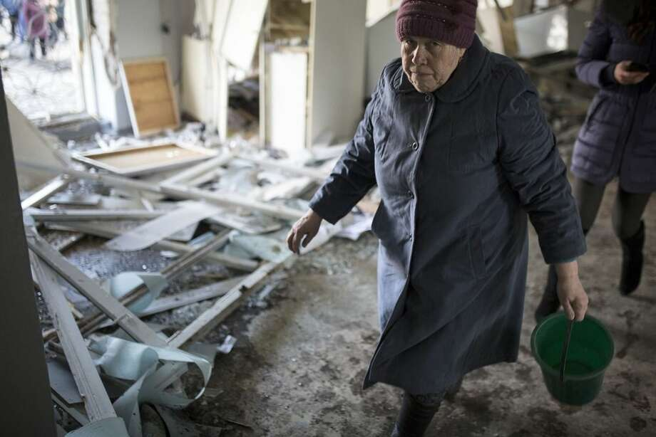 A woman walks in clinic 27, damaged after shelling, in Donetsk, Ukraine, Wednesday, Feb. 4, 2015. Heavy shelling in the rebel stronghold of Donetsk in eastern Ukraine on Wednesday afternoon killed at least five people and damaged a hospital, six schools and five kindergartens, local officials said. (AP Photo/Vadim Braydov)