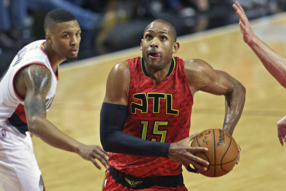 FILE - In this Jan. 20, 2016, file photo, Atlanta Hawks center Al Horford drives past Portland Trail Blazers guard Damian Lillard during the second half of an NBA basketball game in Portland, Ore. The Hawks All-Star said Wednesday, Feb. 17, 2016, he expects to remain in Atlanta, and he is the ideal fit for coach Mike Budenholzer's system. But he will be a free agent this summer, and the Hawks could look to move him if they think they would lose him for nothing in a few months. (AP Photo/Craig Mitchelldyer, File)