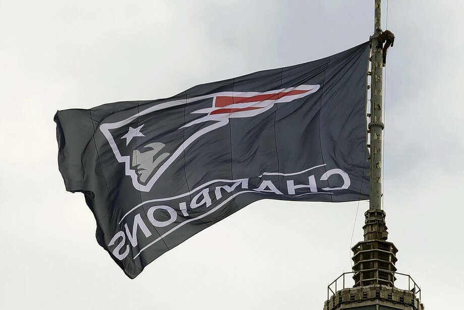 A worker secures a New England Patriots flag on a flagpole atop a building prior to a victory parade in Boston Wednesday, Feb. 4, 2015, to honor the Patriots win over the Seattle Seahawks 28-24 in Super Bowl XLIX Sunday, in Glendale, Ariz. (AP Photo/Steven Senne)