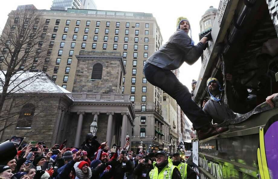 New England Patriots tight end Rob Gronkowski hangs out of a duck boat as fans cheer during a parade in Boston, Wednesday, Feb. 4, 2015, to honor the NFL football team's victory over the Seattle Seahawks in Super Bowl XLIX in Glendale, Ariz.(AP Photo/Charles Krupa)