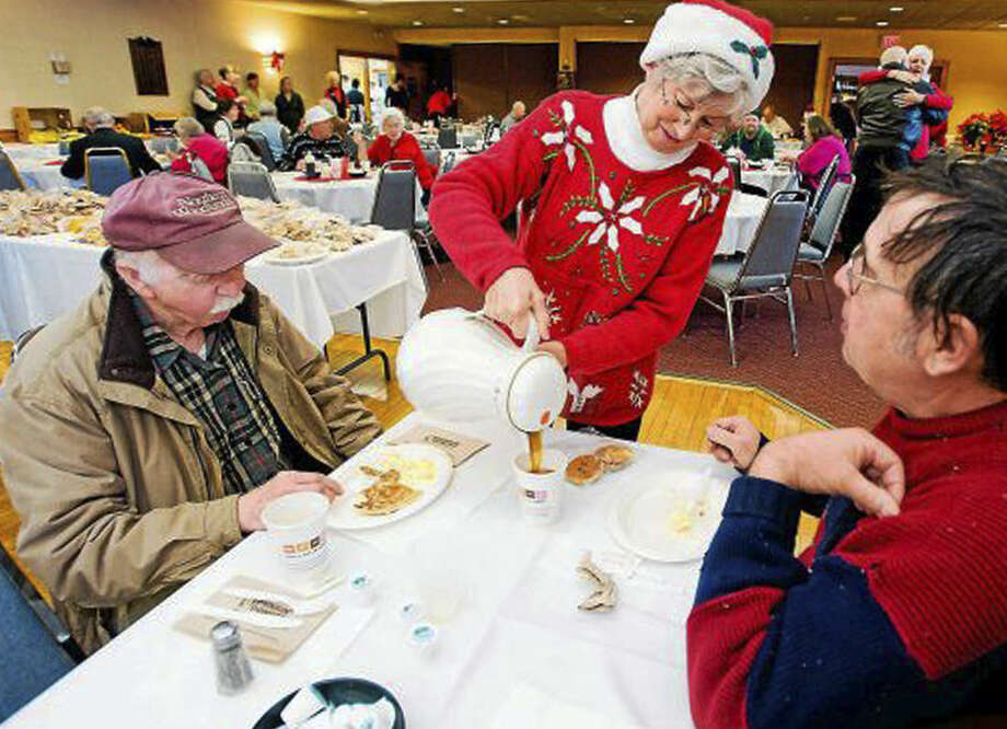 In this December 2011 photo, Connie Howe pours coffee for Ronald Read, left, and Dave Smith during the Charlie Slate Memorial Christmas breakfast at the American Legion in Brattleboro, Vt. Read, a former gas station employee and janitor who died in June 2014 at age 92, had a long-time habit of foraging for firewood but also had a hidden talent for picking stocks. After his death he bequeathed $6 million to his local library and hospital. (AP Photo/Brattleboro Reformer, File)