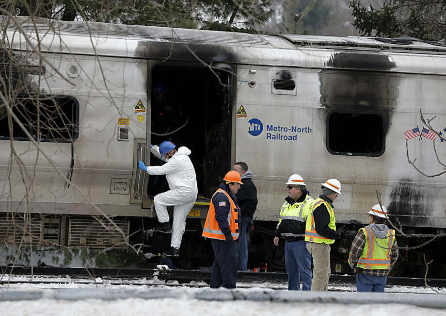 Emergency personnel look over the site of collision between a Metro-North Railroad train and an SUV in Valhalla, N.Y., Wednesday, Feb. 4, 2015. Five train passengers and the SUV's driver were killed in Tuesday evening's crash, in Valhalla, about 20 miles north of New York City. Authorities said the impact was so forceful the electrified third rail came up and pierced the train. (AP Photo/Seth Wenig)