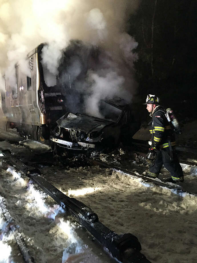 A firefighter walks past the burning wreckage of a Metro-North Railroad passenger train and a vehicle in Valhalla, N.Y., Tuesday, Feb. 3, 2015. Metro-North Railroad spokesman Aaron Donovan says the train struck a vehicle at a railroad crossing about 20 miles north of New York City. (AP Photo/The Journal News, Albert Conte)