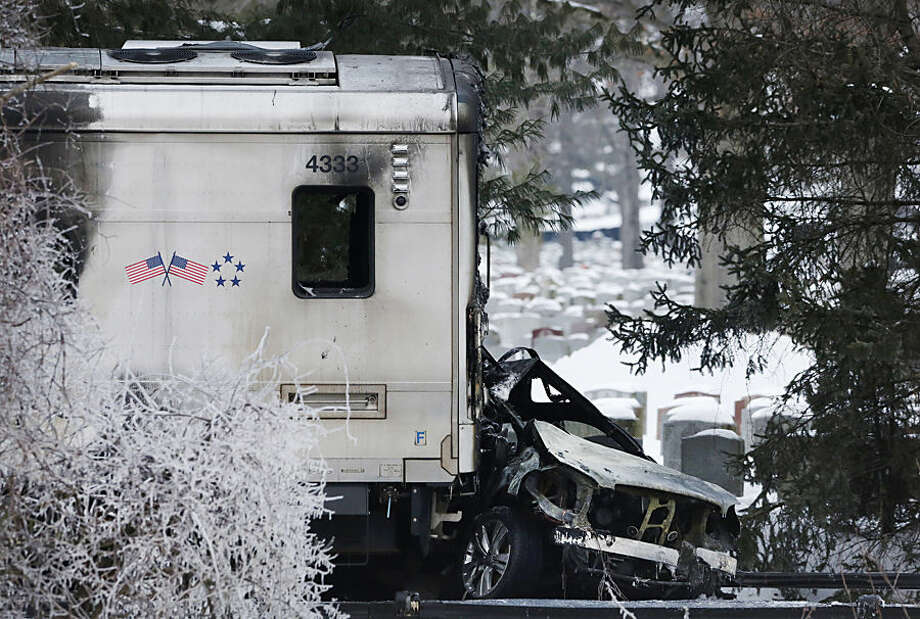 A sports utility vehicle remains crushed and burned at the front of a Metro-North train, Wednesday, Feb. 4, 2015, in Valhalla, N.Y. The commuter train slammed into the SUV stuck on the tracks Tuesday evening, killing the driver and several train passengers, authorities said. (AP Photo/Mark Lennihan)