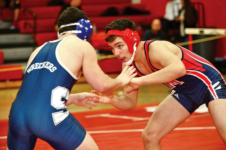 Hour photo / Erik Trautmann Staples High School's John Maragos wrestles Brien McMahon's Jeff Capone during the FCIAC championship wrestling meet at New Canaan High School Saturday.