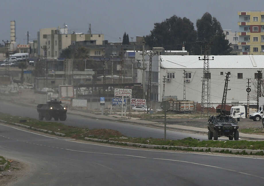 Turkish forces' armoured vehicles patrol at the southeastern town of Nusaybin, Turkey, near the border with Syria, where Turkish security forces are battling militants linked to the outlawed Kurdistan Workers, Party or PKK, Sunday, Feb. 14, 2016, a day after Turkish media reports said a police officer was injured in a clash. The private Dogan news agency said the militants on Saturday detonated an explosive device in the town as a military vehicle was passing by, but no one injured. A second bomb was defused in a controlled explosion. (AP Photo/Lefteris Pitarakis)