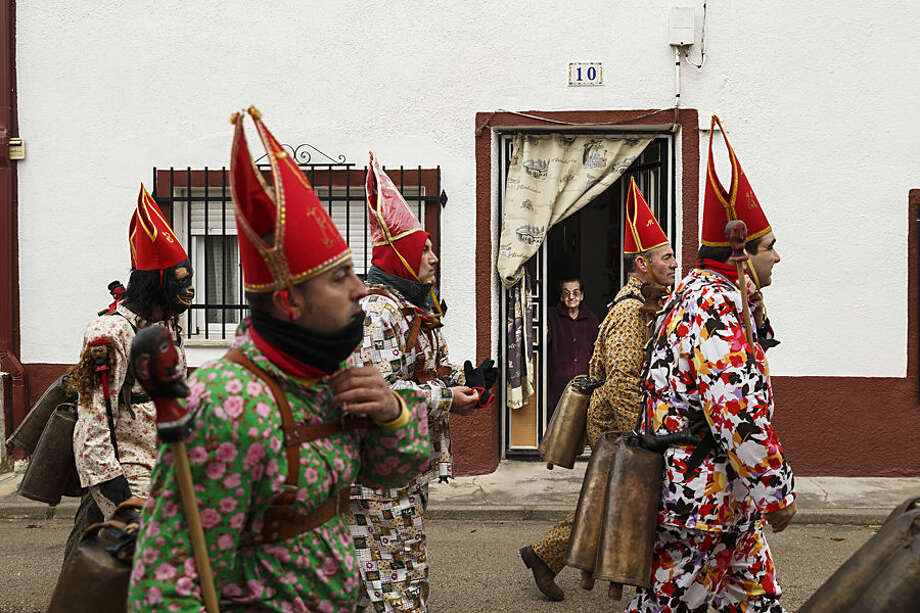 """A woman looks from her home as members of the Endiablada brotherhood march past during the 'Endiablada' traditional festival in Almonacid Del Marquesado, Spain, Tuesday, Feb. 3, 2015. The """"Endiablada"""" (The Brotherhood of the Devils) festivals are celebrated each Feb. 2-3 in the central Spanish town of Almonacid del Marquesado since medieval times or before. In the festival, men from the town dress up as devil-type characters in colorful jumpsuit costumes and red miter hats. They don large heavy copper cowbells around their waists, which clang incessantly as they walk, dance and jump through the town's winding streets and visit the cemetery. The Feb. 3 day procession commemorates the day of Saint Blas. According to a local legend, town shepherds found a statue of the saint and then won a competition with folk from a nearby town to keep the effigy and rang the bells of their animals in celebration. (AP Photo/Daniel Ochoa de Olza)"""