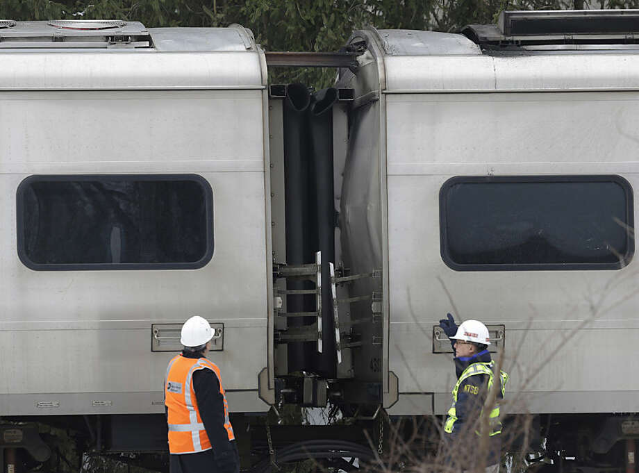 Emergency personnel look at a rail of steel that punctured two cars of a Metro-North Railroad train at the site of an accident in Valhalla, N.Y., Wednesday, Feb. 4, 2015. The packed commuter train slammed into a sport utility vehicle stuck on the tracks and erupted into flames Tuesday night, killing several people and sending hundreds of passengers scrambling for safety, authorities said. (AP Photo/Seth Wenig)