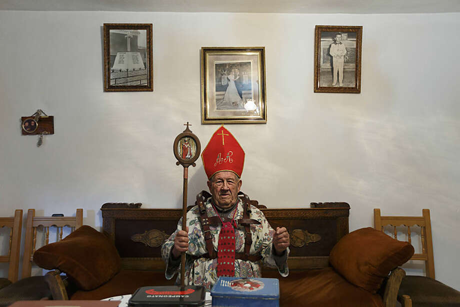 "Aniceto Rodrigo, 78, Diablo Mayor or 'greater devil', poses for pictures inside his home before walking around the village during the 'Endiablada' traditional festival in Almonacid Del Marquesado, Spain, Tuesday, Feb. 3, 2015. The ""Endiablada"" (The Brotherhood of the Devils) festivals are celebrated each Feb. 2-3 in the central Spanish town of Almonacid del Marquesado since medieval times or before. In the festival, men from the town dress up as devil-type characters in colorful jumpsuit costumes and red miter hats. They don large heavy copper cowbells around their waists, which clang incessantly as they walk, dance and jump through the town's winding streets and visit the cemetery. The Feb. 3 day procession commemorates the day of Saint Blas. According to a local legend, town shepherds found a statue of the saint and then won a competition with folk from a nearby town to keep the effigy and rang the bells of their animals in celebration. (AP Photo/Daniel Ochoa de Olza)"