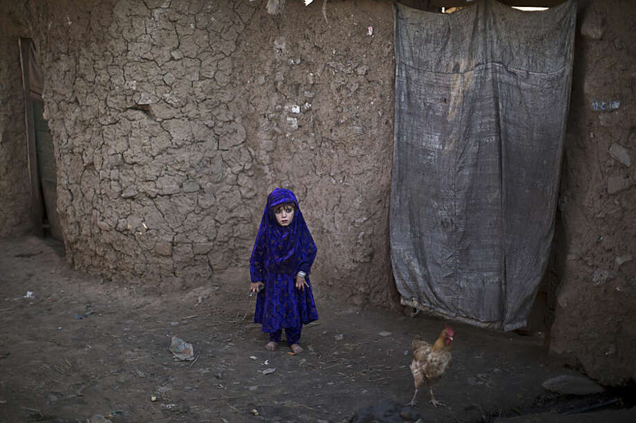An Afghan refugee child stands outside her family's mud home in a slum on the outskirts of Islamabad, Pakistan, Wednesday, Feb. 4, 2015. (AP Photo/Muhammed Muheisen)