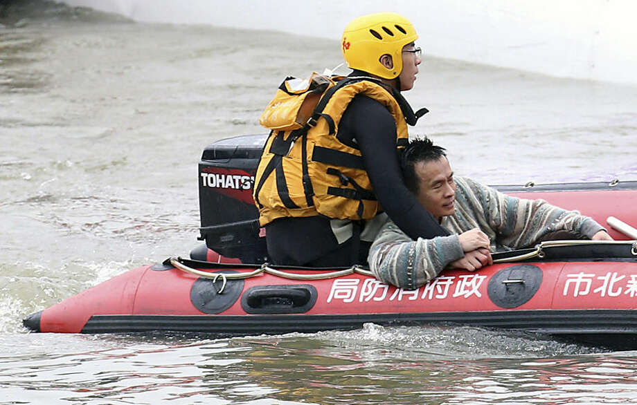 A survivor is rescued from a commercial plane, after it crashed in Taipei, Taiwan, Wednesday, Feb. 4, 2015. The Taiwanese commercial flight with 58 people aboard clipped a bridge shortly after takeoff and crashed into a river in the island's capital on Wednesday morning. (AP Photo) TAIWAN OUT