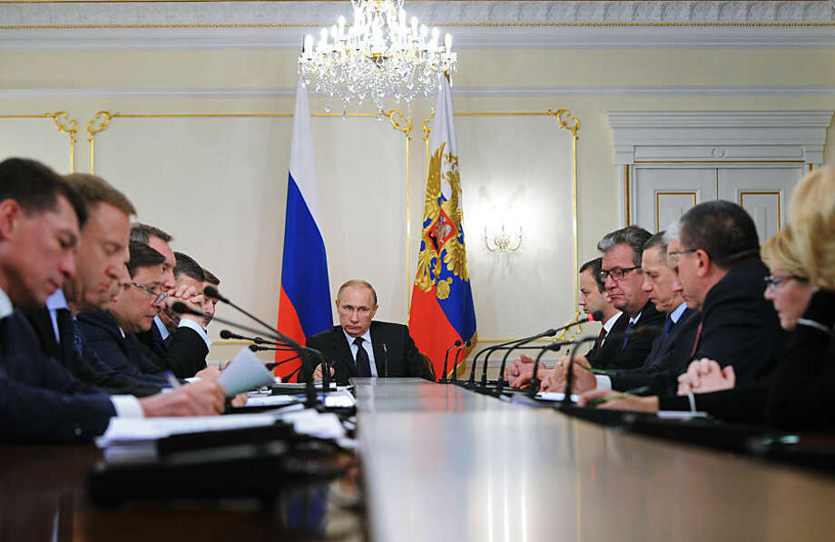 Russian President Vladimir Putin, background centre, heads a cabinet meeting in the Novo-Ogaryovo residence, outside Moscow, Russia, Wednesday, Feb. 4, 2015. Putin has publicly dressed down his government for allowing a business dispute to scrap commuter trains in provincial Russia. (AP Photo/RIA Novosti Kremlin, Mikhail Klimentyev, Presidential Press Service)