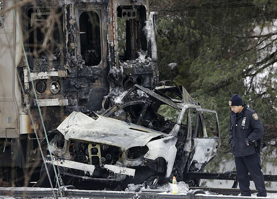A police officer looks at an SUV that was crushed at the front of a Metro-North Railroad train Wednesday, Feb. 4, 2015, in Valhalla, N.Y. Five train passengers and the SUV's driver were killed in Tuesday evening's crash, about 20 miles north of New York City. Authorities said the impact was so forceful the electrified third rail came up and pierced the train. (AP Photo/Mark Lennihan)