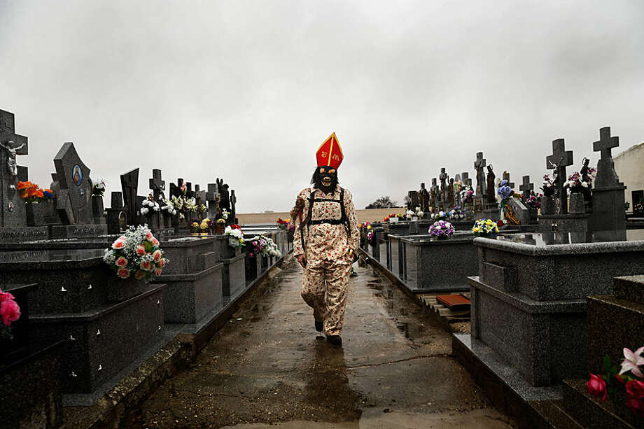 "In this Feb. 2, 2015 picture, a member of the Endiablada brotherhood walks trough the cemetery after paying respect to their deceased fellow believers and relatives during the 'Endiablada' traditional festival in Almonacid Del Marquesado, Spain. The ""Endiablada"" (The Brotherhood of the Devils) festivals are celebrated each Feb. 2-3 in the central Spanish town of Almonacid del Marquesado since medieval times or before. In the festival, men from the town dress up as devil-type characters in colorful jumpsuit costumes and red miter hats. They don large heavy copper cowbells around their waists, which clang incessantly as they walk, dance and jump through the town's winding streets and visit the cemetery. The Feb. 2 procession, the ""Candelaria"" (Candlemas), represents the Virgin Mary presenting baby Jesus to authorities in the temple 40 days after Christmas. The protocol is believed to have caused her some embarrassment and the accompanying bell-clanging characters are thought to be a way of diverting the public's attention. (AP Photo/Daniel Ochoa de Olza)"