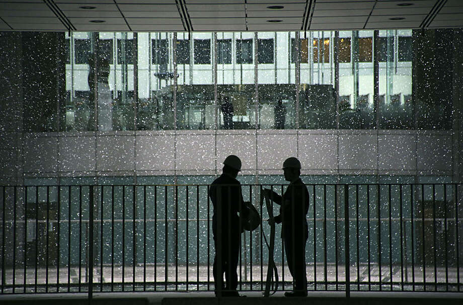 Security guards put a fire hose away at the Tokyo Metropolitan Government building in Tokyo, Thursday, Feb. 5, 2015. (AP Photo/Eugene Hoshiko)