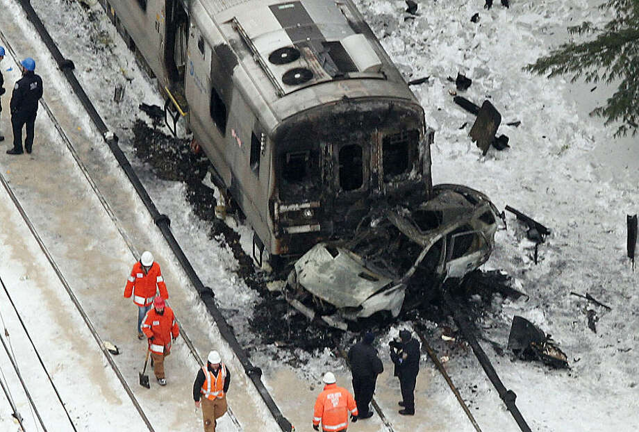 Personnel from various agencies work the scene of a deadly commuter train accident in Valhalla, N.Y., Wednesday, Feb. 4, 2015. The packed Metro-North Railroad train slammed into a SUV stuck on the tracks and erupted into flames Tuesday night, killing some and injuring others, sending hundreds of passengers scrambling for safety, authorities said.(AP Photo/The Journal-News, Frank Becerra Jr.) NYC OUT, NO SALES