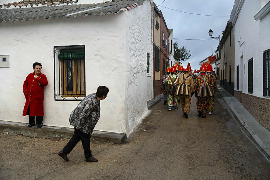 "A woman looks as members of the Endiablada brotherhood march during the 'Endiablada' traditional festival in Almonacid Del Marquesado, Spain, Tuesday, Feb. 3, 2015. The ""Endiablada"" (The Brotherhood of the Devils) festivals are celebrated each Feb. 2-3 in the central Spanish town of Almonacid del Marquesado since medieval times or before. In the festival, men from the town dress up as devil-type characters in colorful jumpsuit costumes and red miter hats. They don large heavy copper cowbells around their waists, which clang incessantly as they walk, dance and jump through the town's winding streets and visit the cemetery. The Feb. 3 day procession commemorates the day of Saint Blas. According to a local legend, town shepherds found a statue of the saint and then won a competition with folk from a nearby town to keep the effigy and rang the bells of their animals in celebration. (AP Photo/Daniel Ochoa de Olza)"