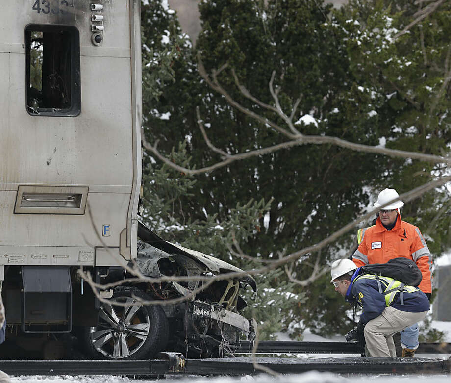 A National Safety Transportation Board employee crouches down to get a better look at the front of a Metro-North Railroad train that collided with an SUV in Valhalla, N.Y., Wednesday, Feb. 4, 2015. Five train passengers and the SUV's driver were killed in Tuesday evening's crash, in Valhalla, about 20 miles north of New York City. Authorities said the impact was so forceful the electrified third rail came up and pierced the train. (AP Photo/Seth Wenig)